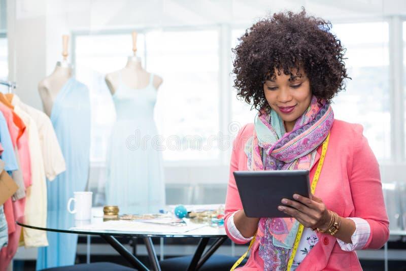 Vrouwelijke manierontwerper die digitale tablet gebruiken stock afbeeldingen