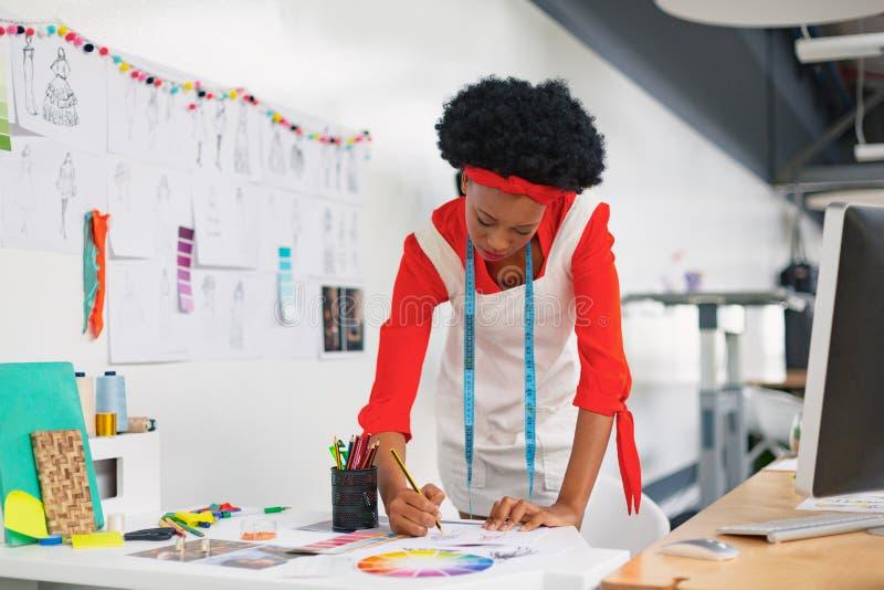 Vrouwelijke manierontwerper die een schets trekken bij bureau stock foto