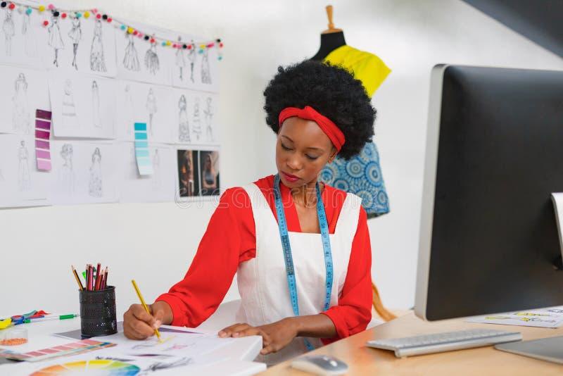 Vrouwelijke manierontwerper die een schets trekken bij bureau royalty-vrije stock afbeelding