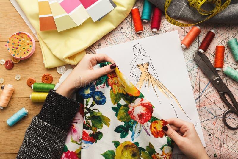 Vrouwelijke manierontwerper die met stoffensteekproef en getrokken illustratie werken royalty-vrije stock afbeeldingen