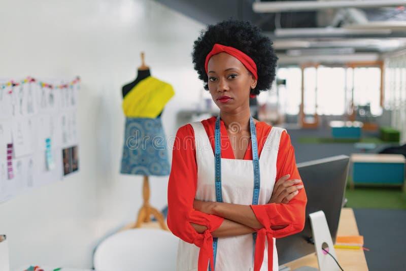 Vrouwelijke manierontwerper die zich met die wapens bevinden in ontwerpstudio worden gekruist royalty-vrije stock foto