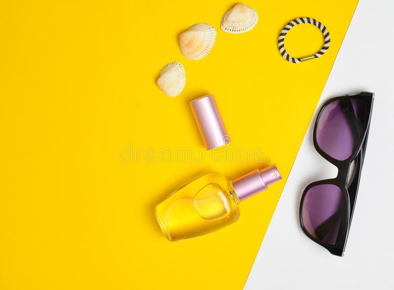 Vrouwelijke maniertoebehoren op een gele witte pastelkleurachtergrond Zonnebril, parfumfles, shells De Toebehoren van het de zome royalty-vrije stock fotografie