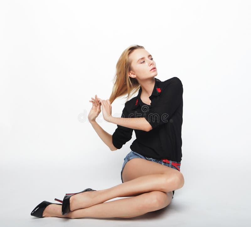 Vrouwelijke mannequin die vrijetijdskleding dragen en op de vloer zitten royalty-vrije stock foto's