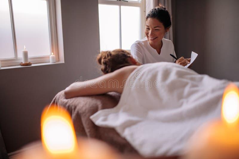 Vrouwelijke massagetherapeut die aan vrouw op wellnesscentrum spreken stock afbeelding
