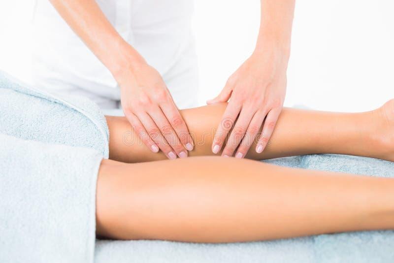 Vrouwelijke masseur die het been van de vrouw masseren stock afbeeldingen