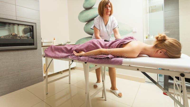Vrouwelijke masseuse die massage met hete stenen doen royalty-vrije stock afbeelding