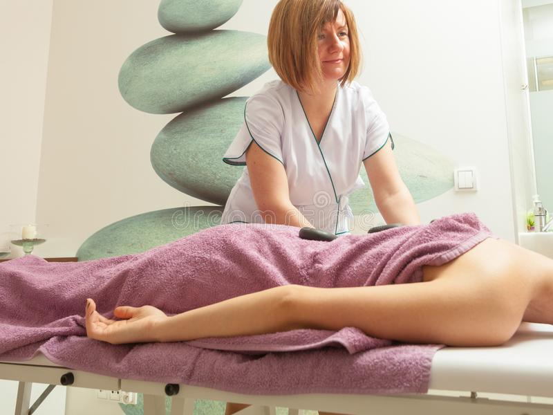 Vrouwelijke masseuse die massage met hete stenen doen stock foto's