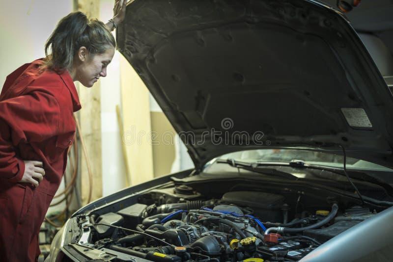 Vrouwelijke mechanische het inspecteren motor van een auto stock foto