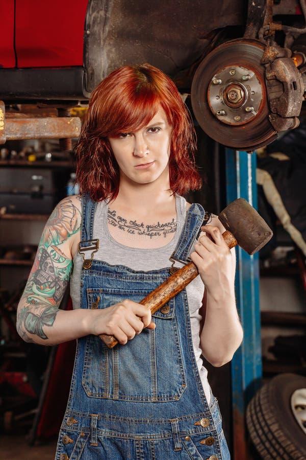 Vrouwelijke mechanische holdings rubberhouten hamer stock foto
