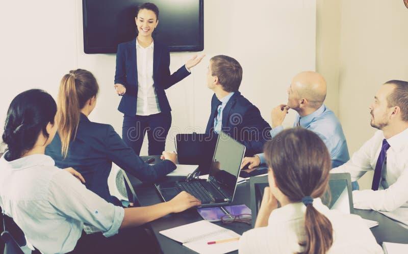 Vrouwelijke medewerker die presentatie maken tijdens vergadering stock foto