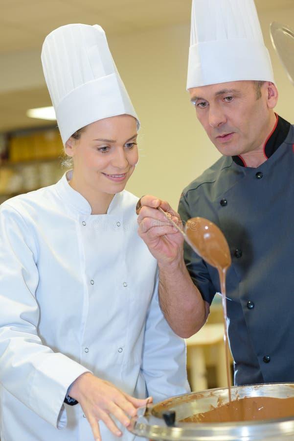 Vrouwelijke medewerker en gebakjechef-kok die karamelbovenste laagje maken royalty-vrije stock afbeeldingen