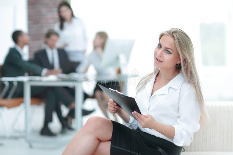 Vrouwelijke medewerker met de notulen van de vergadering over de achtergrond van het bureau royalty-vrije stock afbeelding