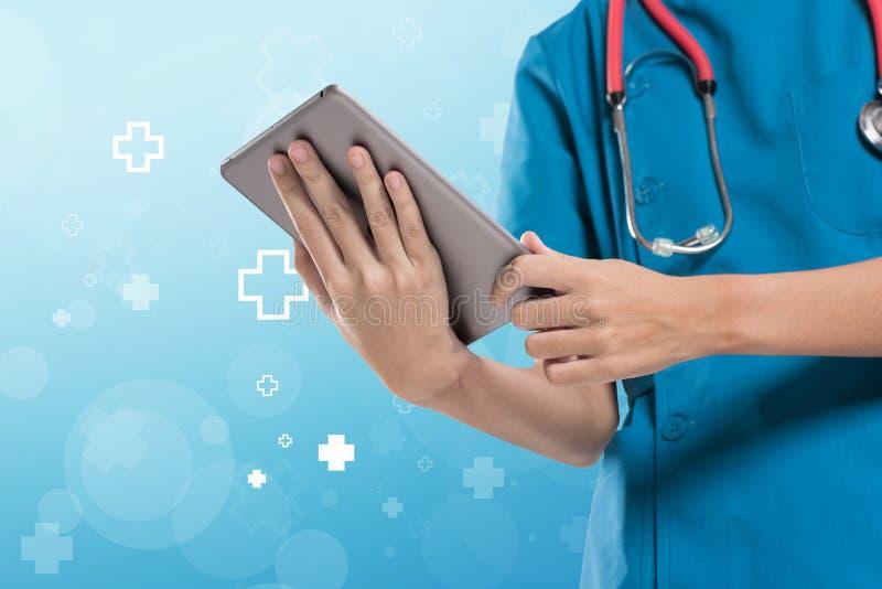 Vrouwelijke medische artsenverpleegster die tablet op blauwe achtergrond gebruiken grad royalty-vrije stock foto