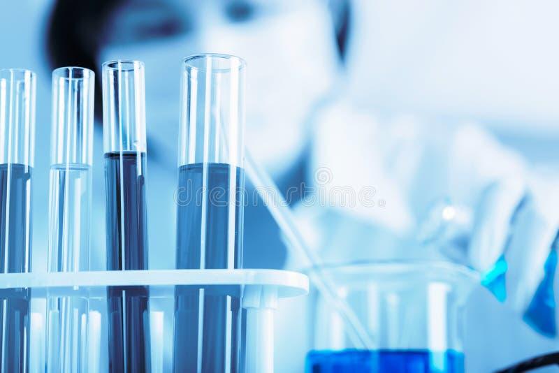 Vrouwelijke medische of wetenschappelijke onderzoeker die reageerbuis op arbeid met behulp van stock afbeeldingen