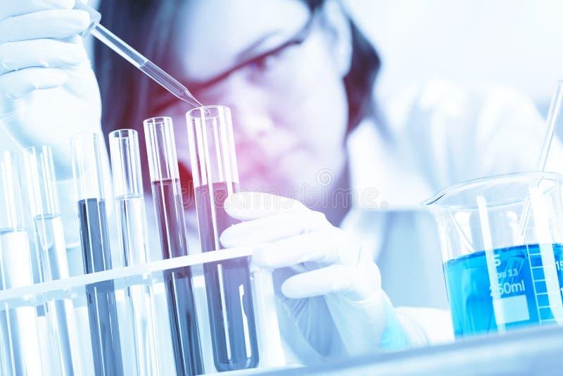 Vrouwelijke medische of wetenschappelijke onderzoeker die reageerbuis op arbeid met behulp van royalty-vrije stock afbeeldingen