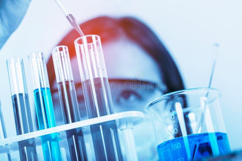 Vrouwelijke medische of wetenschappelijke onderzoeker die reageerbuis op arbeid met behulp van stock afbeelding