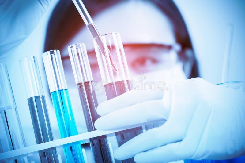Vrouwelijke medische of wetenschappelijke onderzoeker die reageerbuis op arbeid met behulp van royalty-vrije stock foto's