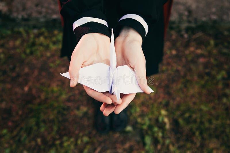 Vrouwelijke meisjeshanden die origamidocument kraanvogel met achtergrond van gras, de Japanse eenvormige school houden van de mei stock fotografie