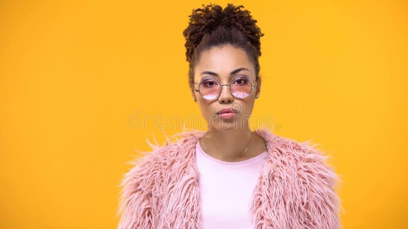 Vrouwelijke millennial in modieuze doek die in camera op heldere achtergrond, model kijken royalty-vrije stock afbeelding