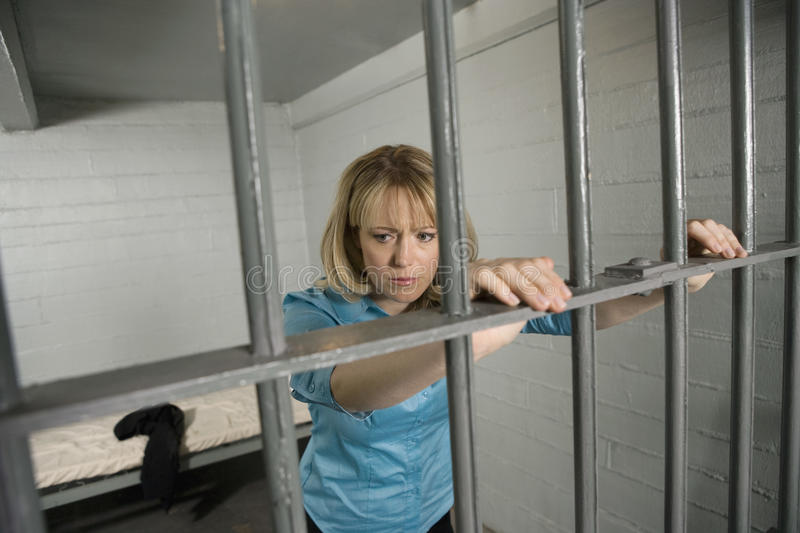 Vrouwelijke Misdadiger achter de tralies stock fotografie