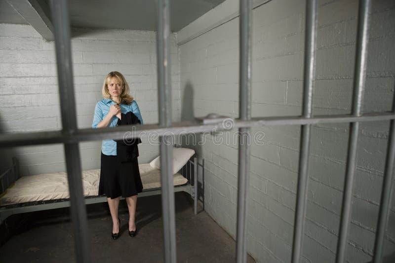 Vrouwelijke Misdadiger achter de tralies stock foto's