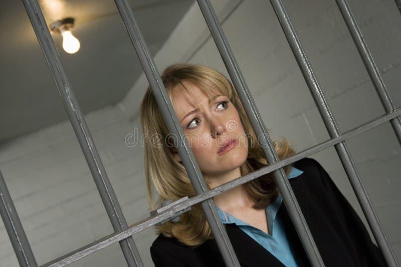 Vrouwelijke Misdadiger achter de tralies in Gevangenis stock afbeelding