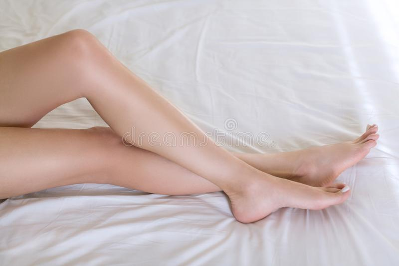 Vrouwelijke mooie benen met goed verzorgde natuurlijke huid op wit beddegoed De Kaukasische vrouw kruist haar enkels, ivoorpedicu stock afbeeldingen