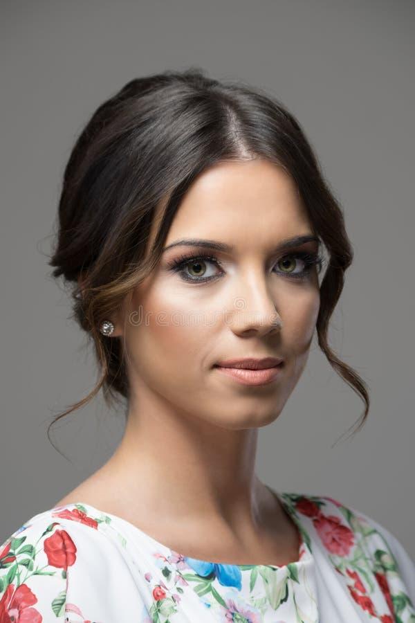 Vrouwelijke mooie jonge vrouw die met broodjeskapsel camera bekijken royalty-vrije stock foto's
