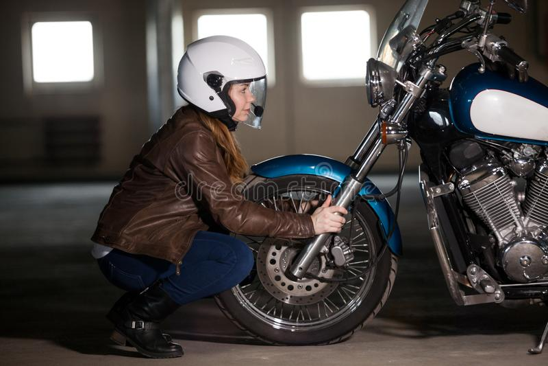 Vrouwelijke motorrijder die tegenover wiel van bijlfiets zitten, wielvork houden en in koplamplamp kijken stock foto's