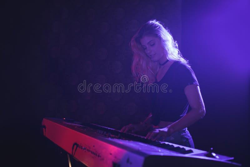 Vrouwelijke musicus het spelen piano op stadium in nachtclub royalty-vrije stock foto's