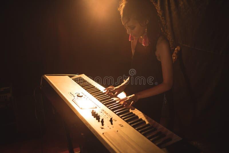 Vrouwelijke musicus het spelen piano in verlichte nachtclub stock fotografie