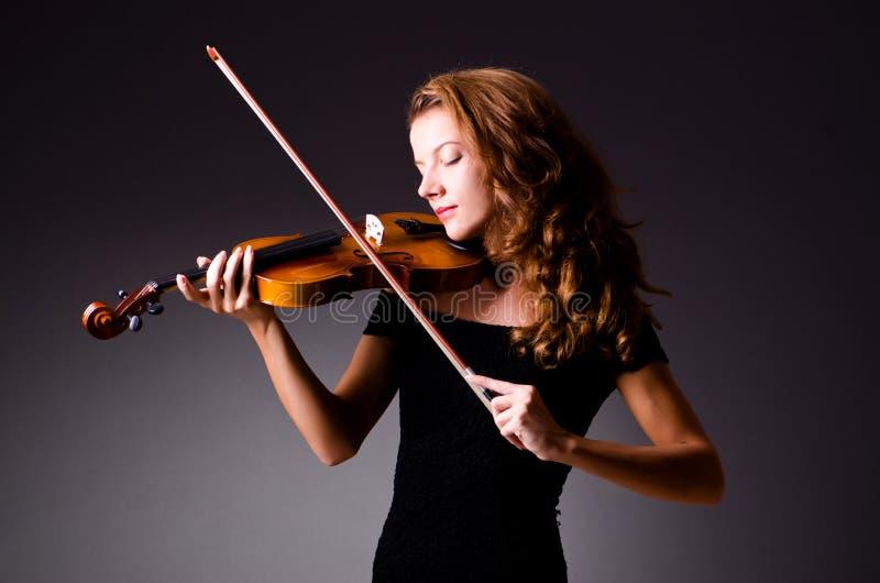 Vrouwelijke muzikale speler tegen donkere achtergrond stock afbeeldingen