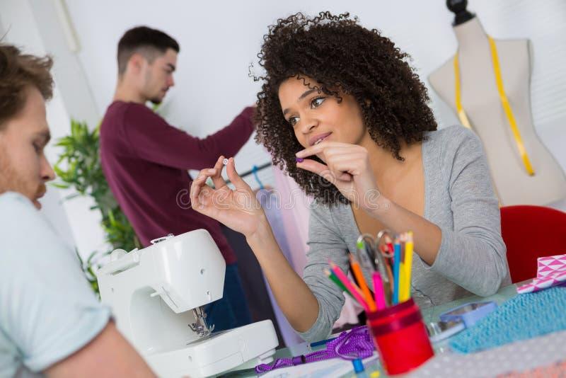 Vrouwelijke naaister die met naaimachine werken stock foto's