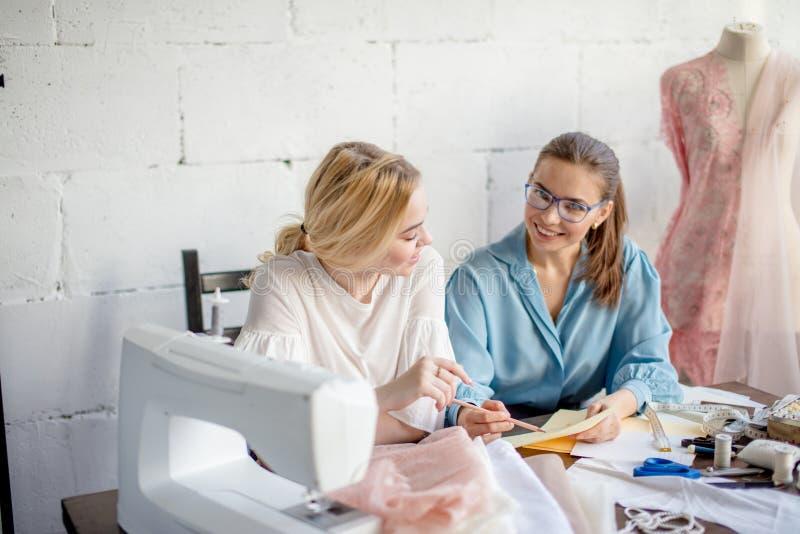 Vrouwelijke naaister die ontwerp tonen aan haar cliënt, die samen op workshop zitten stock fotografie