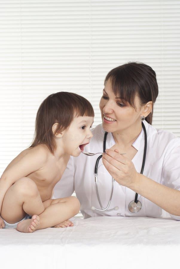 Vrouwelijke octor die geneesmiddelen geven aan kind stock fotografie