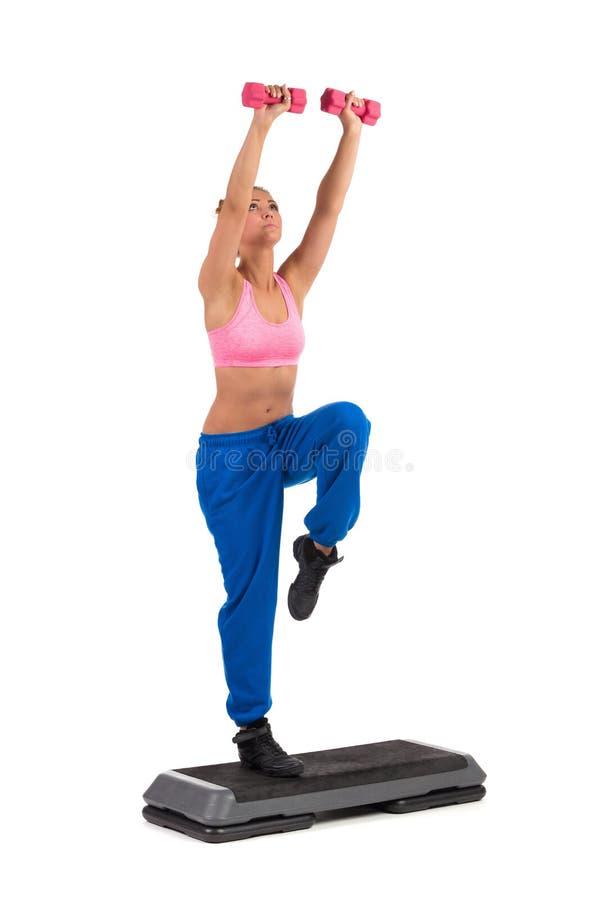 Vrouwelijke Oefening op Aërobe Stap met Handgewichten stock foto's