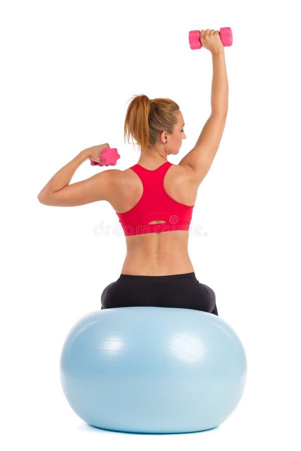 Vrouwelijke Oefening op Geschiktheidsbal met Handgewichten stock foto's