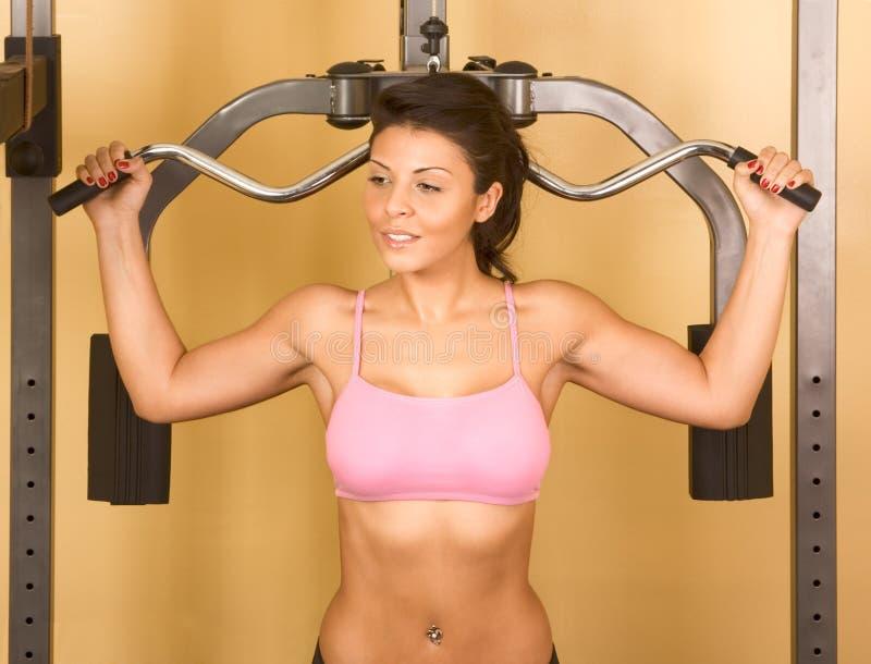 Vrouwelijke oefeningen bij gewicht-opheffende machine stock foto's