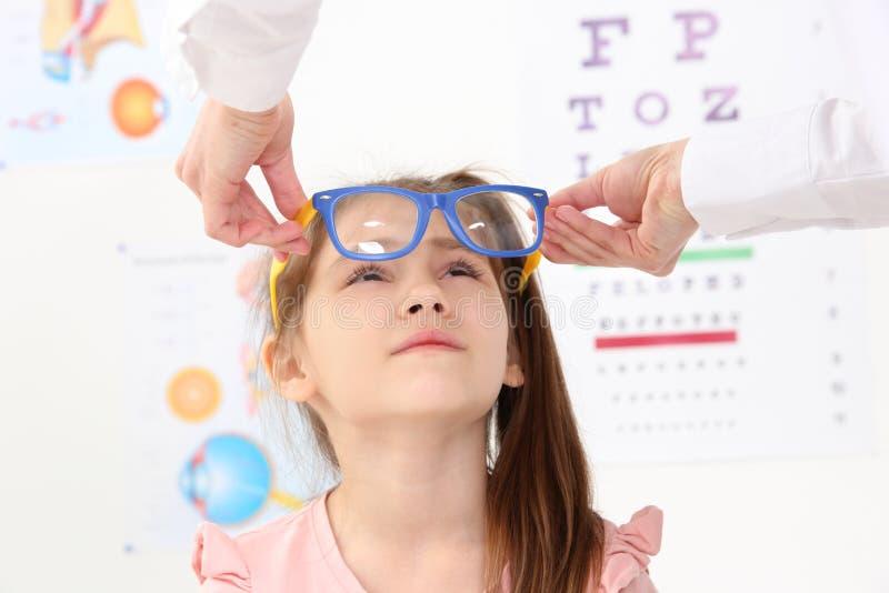 Vrouwelijke oftalmoloog die glazen op meisje zetten royalty-vrije stock foto's