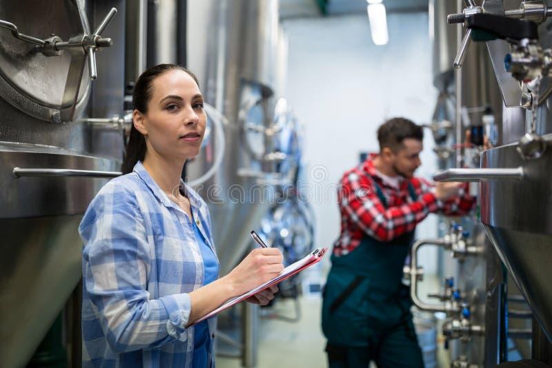 Vrouwelijke onderhoudsarbeider het testen brouwerijmachine royalty-vrije stock fotografie
