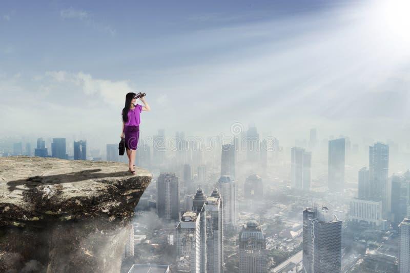 Vrouwelijke ondernemer die door verrekijkers kijken royalty-vrije stock afbeeldingen