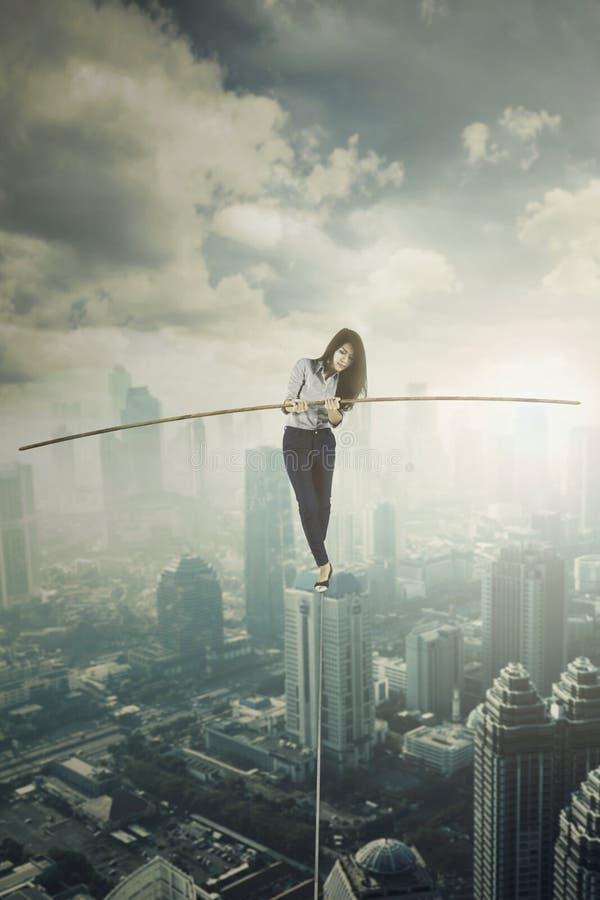 Vrouwelijke ondernemer die op de kabel lopen stock foto