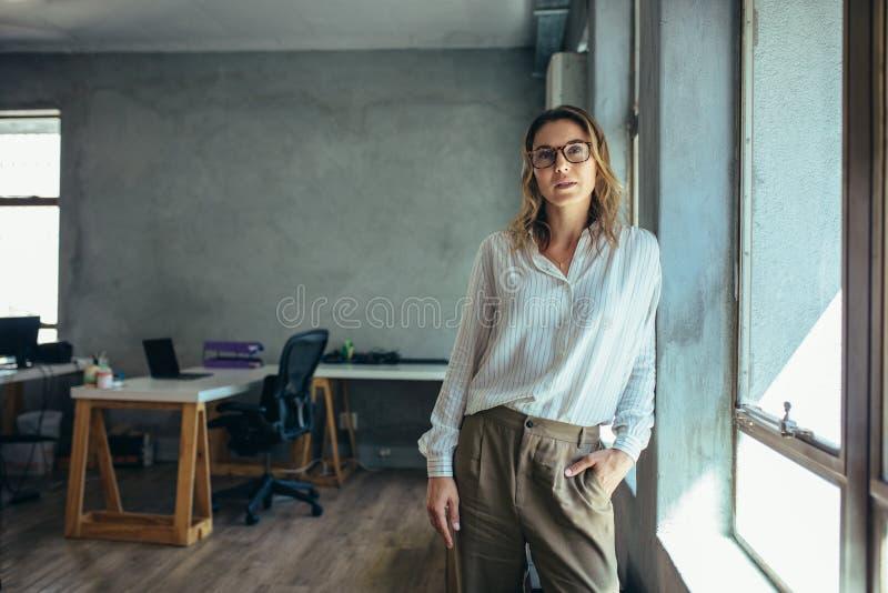 Vrouwelijke ondernemer in haar bureau stock afbeelding