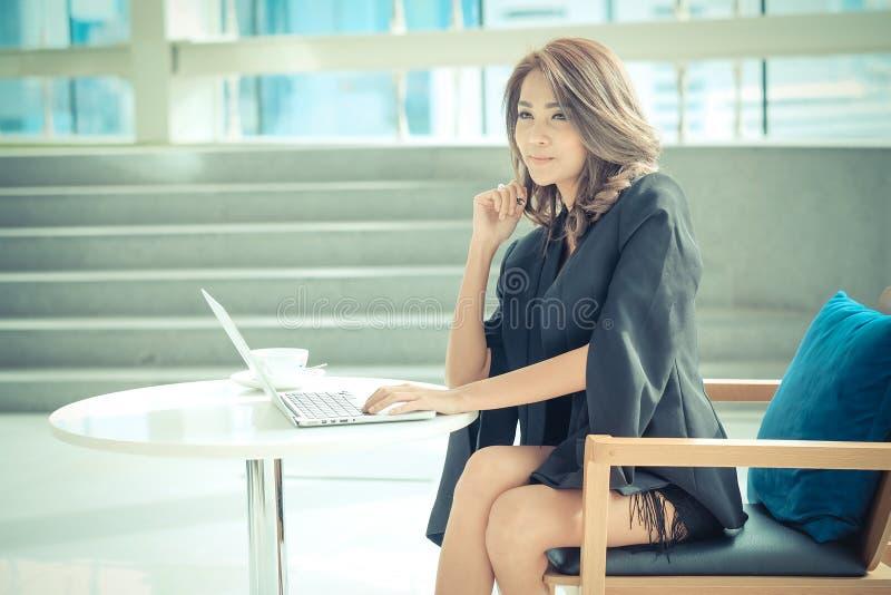 Vrouwelijke ondernemer het werk zitting bij een bureau stock foto