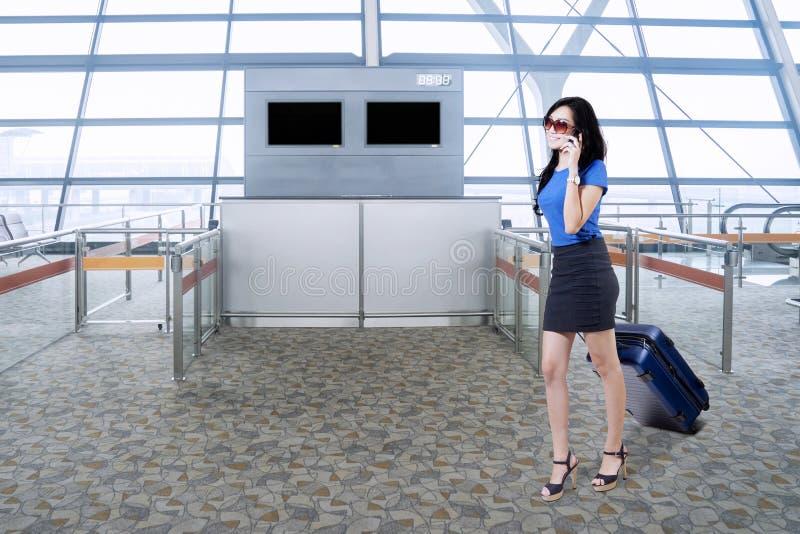 Vrouwelijke ondernemer met smartphone in luchthaven stock afbeeldingen
