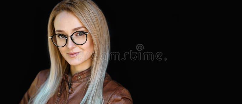 Vrouwelijke Oogglazen, Portret van mooie glimlachende jonge vrouw die het zwarte modieuze optische kader van ontwerpglazen draagt stock foto's