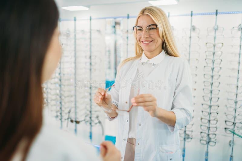 Vrouwelijke opticien en klanten shooses glazen royalty-vrije stock afbeeldingen