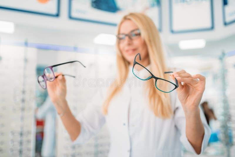 Vrouwelijke opticien tegen showcase met glazen royalty-vrije stock afbeelding