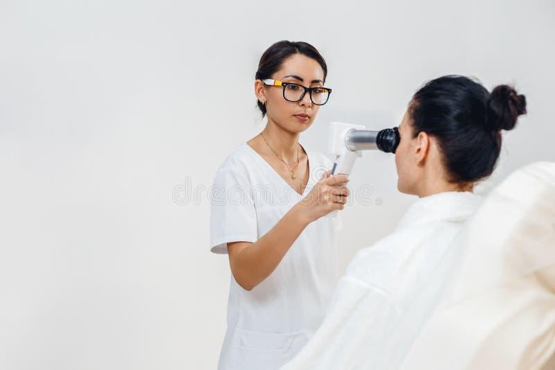 Vrouwelijke optometrist die met speciaal materiaal geduldige visie controleren bij oogkliniek royalty-vrije stock afbeelding