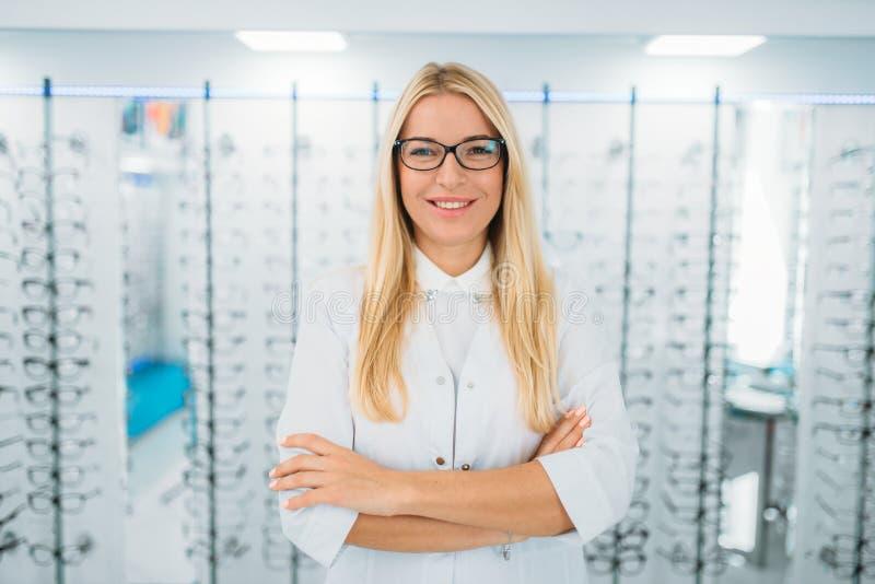 Vrouwelijke optometrist tegen showcase met glazen stock afbeelding